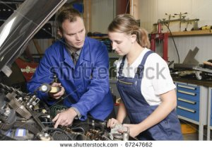 stock-photo-auto-mechanic-shows-the-female-trainee-maintenance-of-the-engine-in-workshop-in-front-of-a-car-67247662